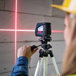 Female worker on the building site. Beautiful young woman with line laser level. House construction.